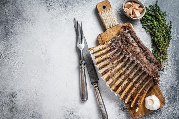 Holzkohle gegrilltes französisches rack mit lammrippenkoteletts auf schneidebrett