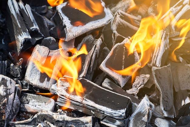 Holzkohle in flammen zum grillen auf einem picknick.