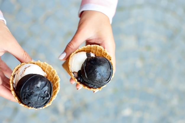 Holzkohle- und vanilleeis der frau in der hand