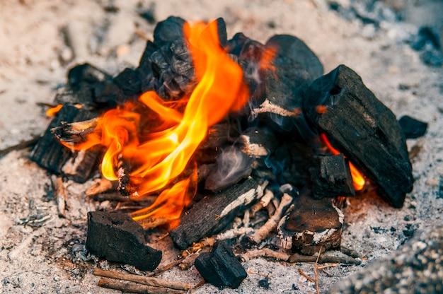 Holzkohlebriketts, die für den grill anzünden. feuer kohlen. holzkohle feuer