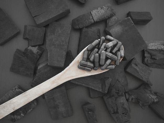 Holzkohlekapsel und holzkohle auf schwarzem hintergrund zur heilung von durchfall und zur aufnahme von giftstoffen im darm