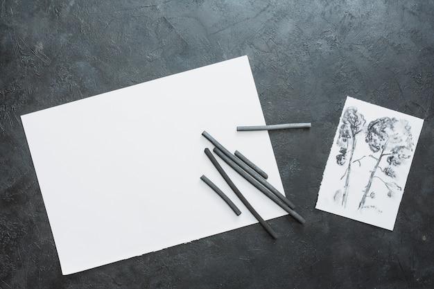 Holzkohlenstock mit gezogenem papier und schwarzem weißem papierblatt