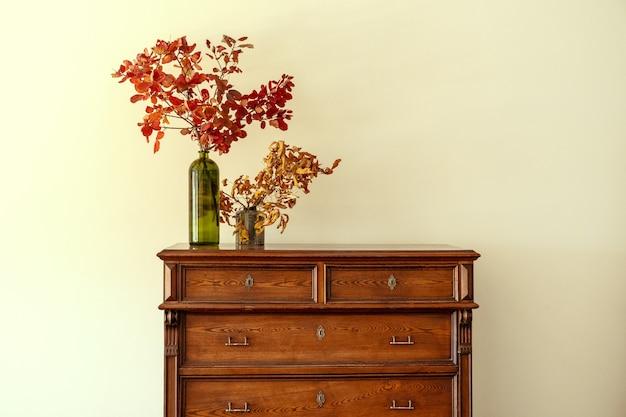 Holzkommode mit blumenzweigen in vase