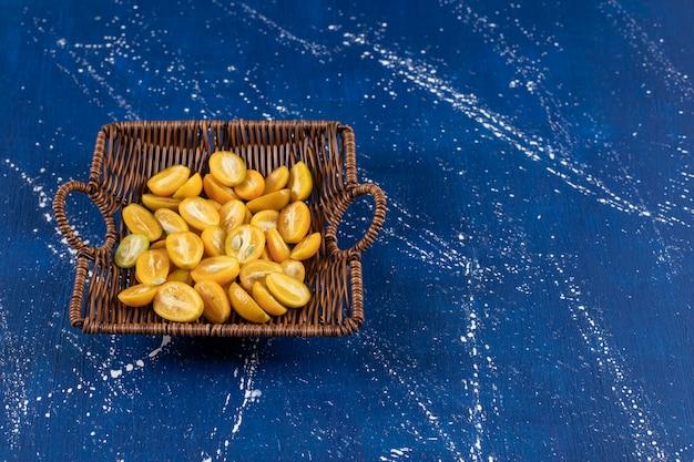 Holzkorb mit geschnittenen kumquat-früchten auf marmoroberfläche