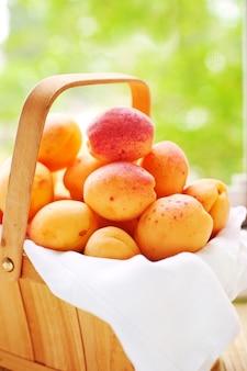 Holzkorb mit saftigen früchten vor grünem frühlingshintergrund