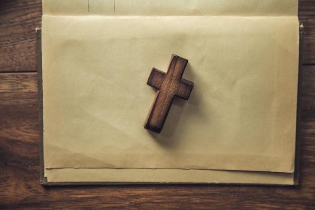 Holzkreuz auf dem weinlesepapier auf braunem hintergrund