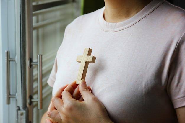 Holzkreuz auf frauenhand gegen ihre brust