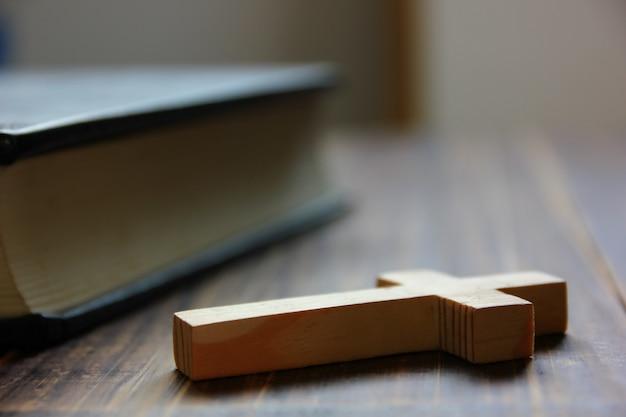 Holzkreuz mit bibel auf braunem holzboden