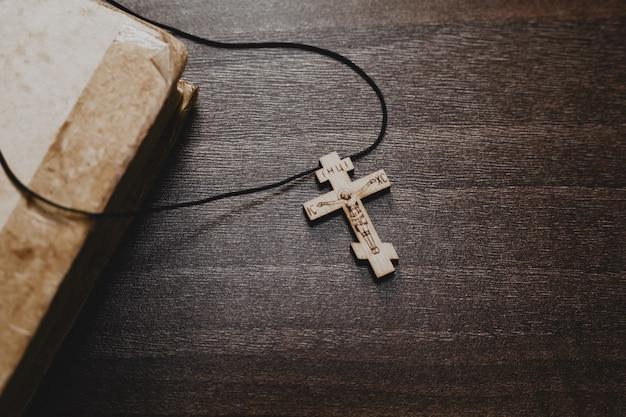Holzkreuz und altes bibelbuch auf holztisch