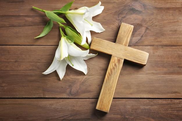 Holzkreuz und weiße lilie auf dem tisch Premium Fotos