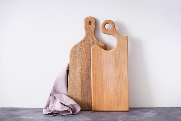 Holzküchenbrett und küchentuch auf grauem hintergrund, platz für text.