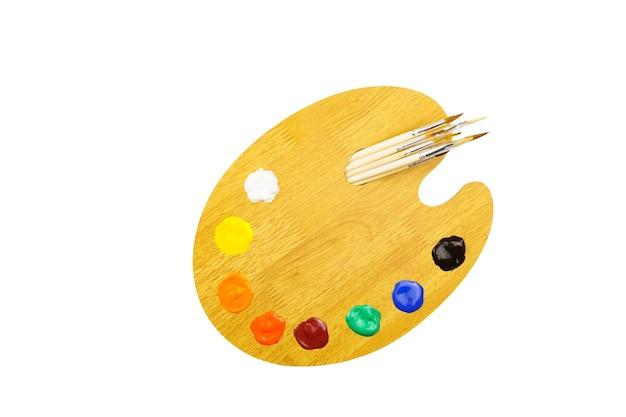 Holzkunstpalette mit farben und pinseln lokalisiert auf weißer wand.