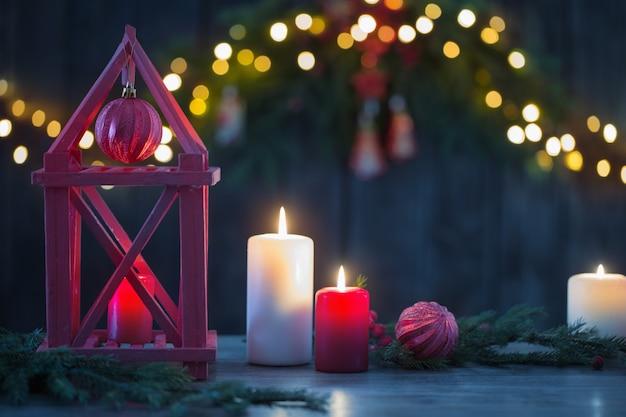 Holzlaterne mit kerzen und weihnachtszweigen auf holz