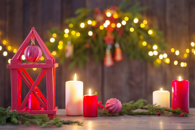 Holzlaterne mit kerzen und weihnachtszweigen auf holzrücken