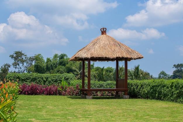 Holzlaube mit strohdach zum entspannen im tropischen garten. insel bali, ubud, indonesien