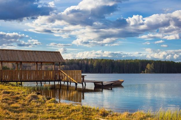 Holzlaube und pier am ufer des frühlingssees
