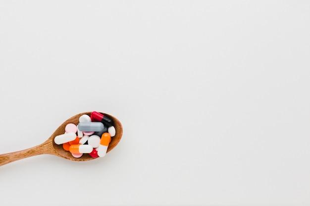 Holzlöffel der draufsicht gefüllt mit pillen und kopierraum
