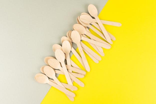 Holzlöffel für fast food liegen an der kreuzung von grauem und gelbem hintergrund