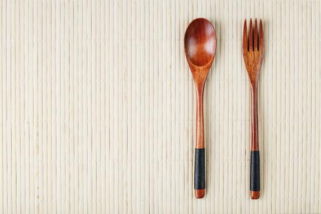 Holzlöffel, gabel auf bambusunterlage. asiatisches lebensmittelhandwerkskonzept.