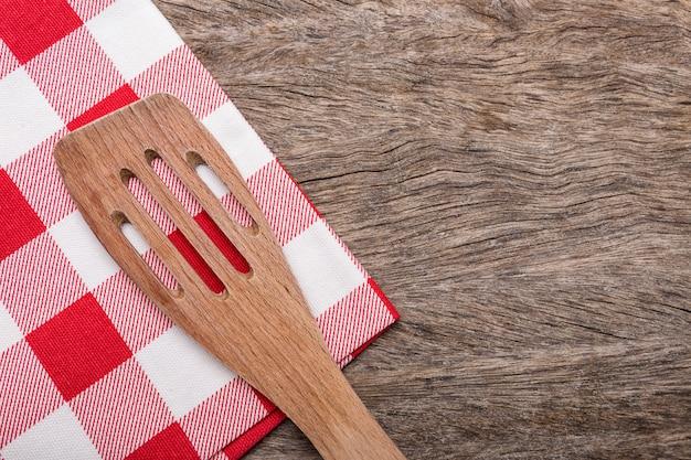Holzlöffel, gabel auf roter serviette für einen tisch. auf holzbeschaffenheit.