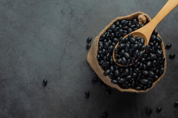 Holzlöffel in einen sack voller schwarzer bohnen legen