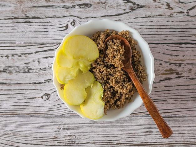 Holzlöffel in einer tasse mit quinoa-brei und apfel. gesunde ernährung. flach liegen.