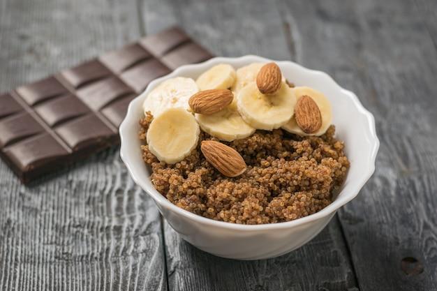 Holzlöffel in einer tasse quinoa-brei und schwarzer schokolade. gesunde ernährung.