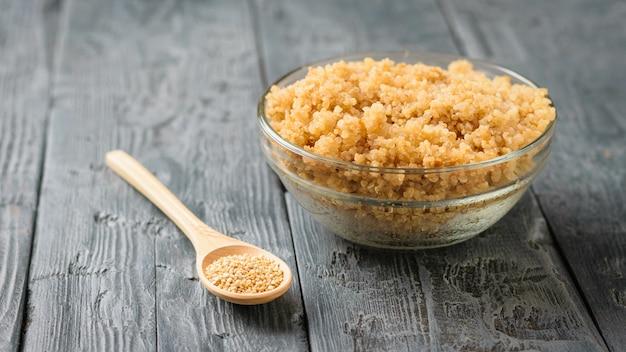 Holzlöffel mit quinoa und eine glasschüssel mit der gekochten quinoa auf einem schwarzen holztisch