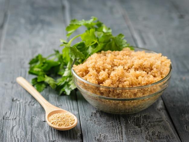 Holzlöffel mit quinoa und eine glasschüssel mit gekochter quinoa und petersilie auf einem schwarzen holztisch.