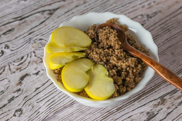 Holzlöffel und apfelscheiben in einer schüssel quinoa-brei. gesunde ernährung.