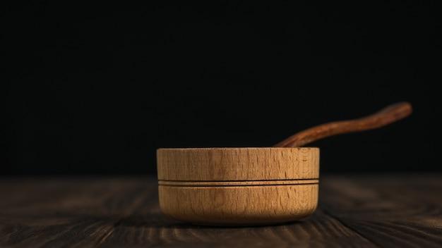 Holzlöffel und holzschale auf einem dunklen holztisch. satz rustikale gerichte auf dem tisch.