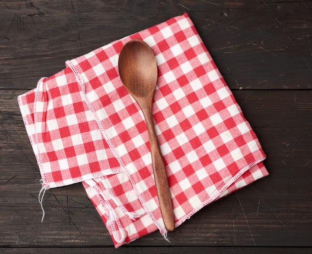 Holzlöffel und rotes textilküchentuch auf braunem hölzernem hintergrund