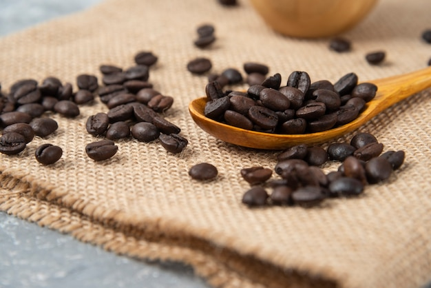 Holzlöffel voller gerösteter kaffeebohnen auf sackleinen.
