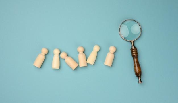 Holzmänner und eine lupe auf blauem grund. rekrutierungskonzept, suche nach talentierten und fähigen mitarbeitern, karriereentwicklung, flat lay
