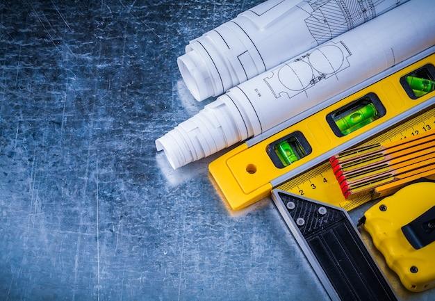 Holzmeter blaupausen und maßband des quadratischen linealkonstruktionsniveaus auf metallischem hintergrundgebäude und architekturkonzept