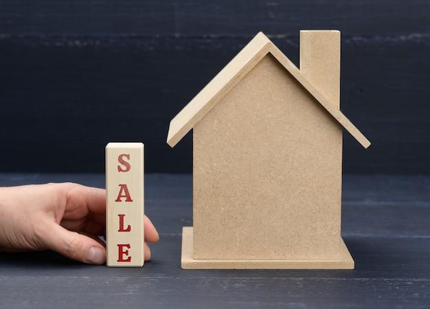 Holzmodell eines hauses und einer hand hält einen block mit einer inschrift verkauf auf einer blauen oberfläche. hausverkaufskonzept, immobilieninvestition, maklerdienstleistungen