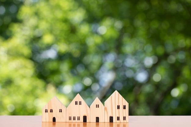 Holzmodellhaus lokalisiert auf unscharfem grünem blatthintergrund