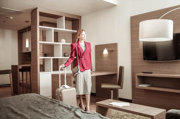 Holzmöbel. schöne stilvolle geschäftsfrau, die zum gemütlichen zimmer des hotels mit holzmöbeln kommt