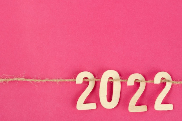 Holznummer 2022 und seil auf rosafarbenem hintergrund mit kopienraum für ihren text oder ihre nachricht.