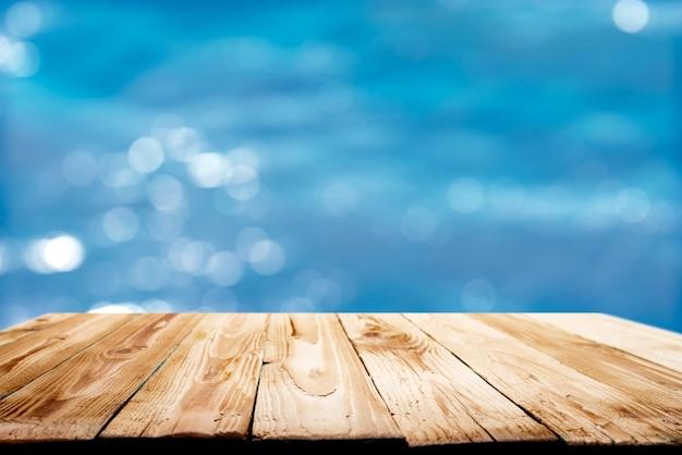 Holzoberfläche gegen defokussierten blauen meereshintergrund während des tages