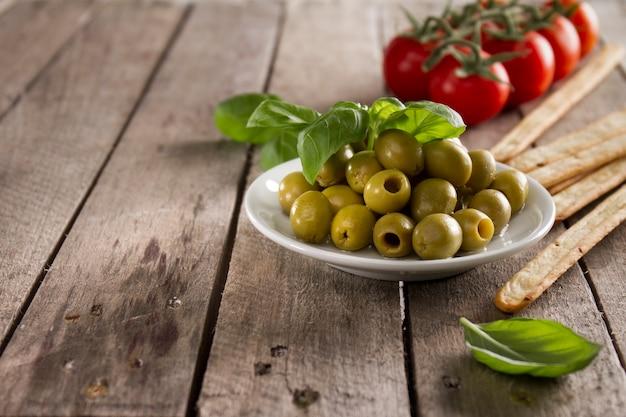 Holzoberfläche mit oliven und tomaten hintergrund