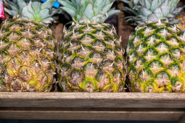 Holzöse box mit exotischer ananas auf supermarkttheke