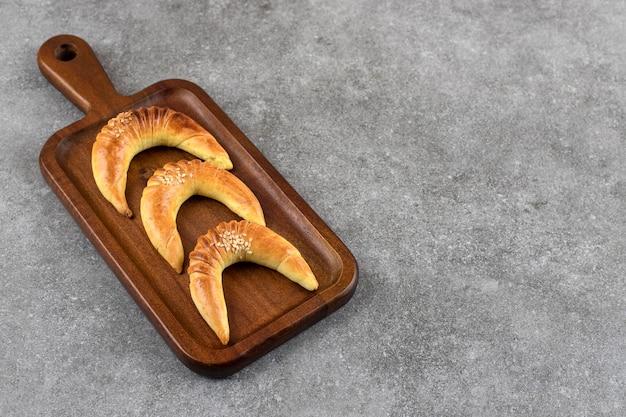 Holzpastete von drei köstlichen halbmondförmigen vanillekeksen auf marmortisch.