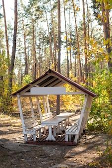 Holzpavillon mit tisch und bänken zum entspannen und picknicken an einem wochenende in der natur