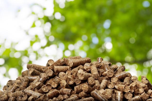 Holzpellets auf einem grünen hintergrund. biokraftstoffe.