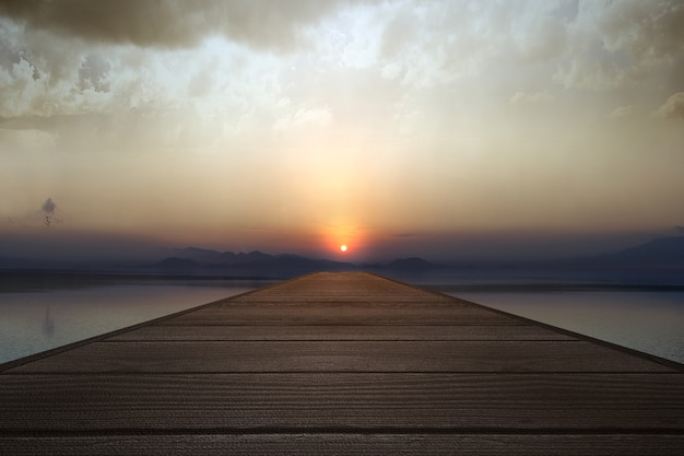 Holzpier mit seeblick und sonnenuntergangshimmelhintergrund