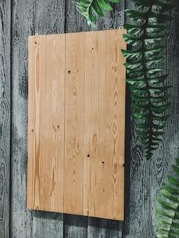 Holzplan, der an der wand hängt mit grünen blättern an der seite