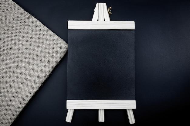 Holzplankentisch für grafikständerprodukt. menü black board isoliert auf schwarzem hintergrund.