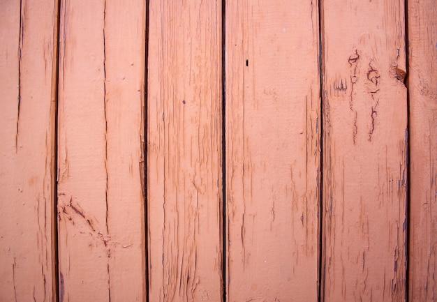Holzplankenwand mit brauner farbe bemalt. die farbe ist rissig und blättert ab.