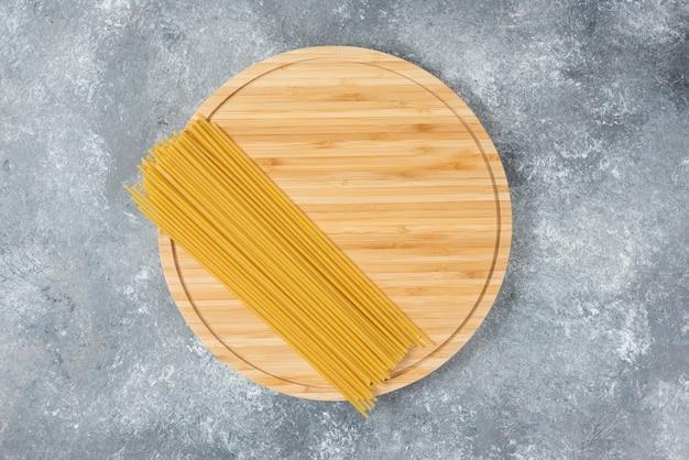 Holzplatte aus rohen, trockenen spaghetti auf marmoroberfläche.